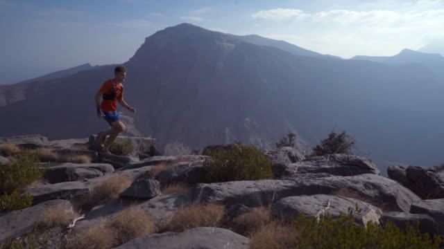 vídeos de stock, filmes e b-roll de corredor de trilha movimentando-se ao longo da borda do penhasco - falésia