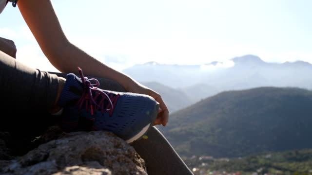 stockvideo's en b-roll-footage met trail runner pauzes op rock to tie schoenen - schoen
