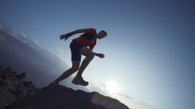trail runner running and jumping off rock - rock object stock videos and b-roll footage
