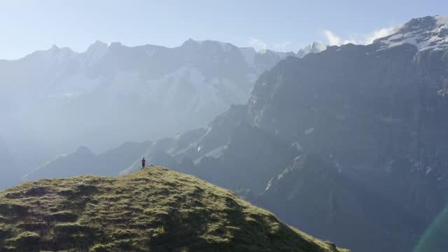 vidéos et rushes de trail runner runs along grassy ridge with snow capped peaks behind. - sommet montagne