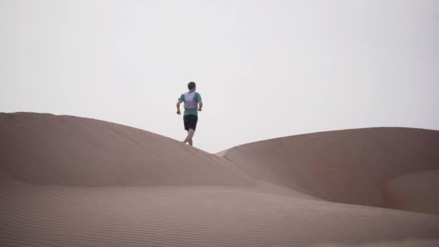 vídeos de stock, filmes e b-roll de trilha corredor corre sobre dunas no deserto - geração z