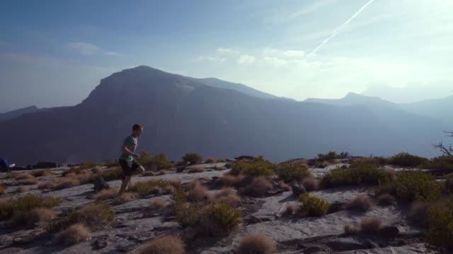 vídeos de stock, filmes e b-roll de passos de corredor de trilha ao longo da borda do penhasco acima do desfiladeiro - falésia