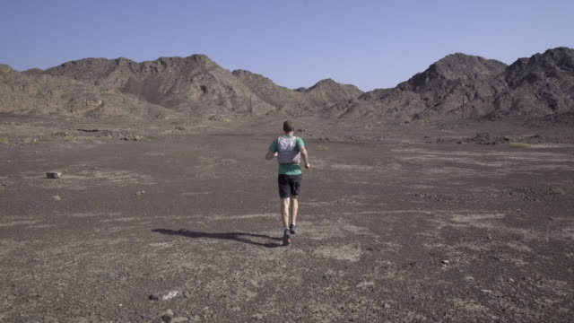 Trail runner striding towards desert landscape