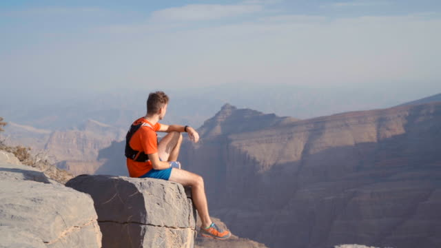 Trail runner takes break on cliff overlooking canyon