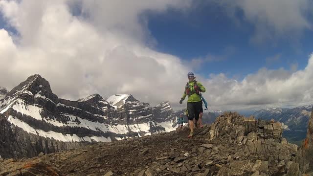 trail runners ascend path along mountain ridge, past summit - bastoncino da sci video stock e b–roll