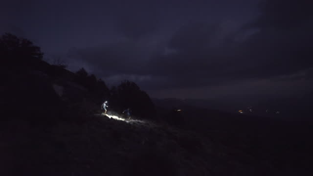 trail runners with headlamps running mountain trails at night - head torch stock videos & royalty-free footage