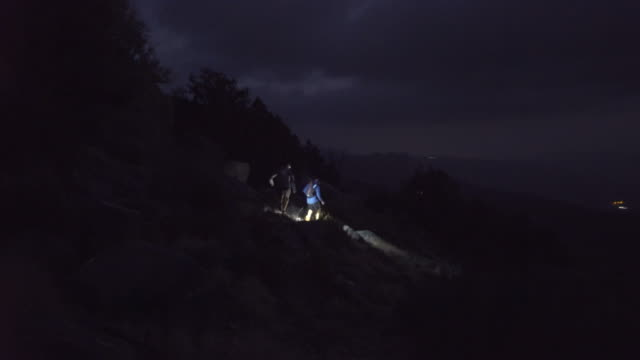 trail runners with headlamps running mountain trails at night - electric torch stock videos & royalty-free footage