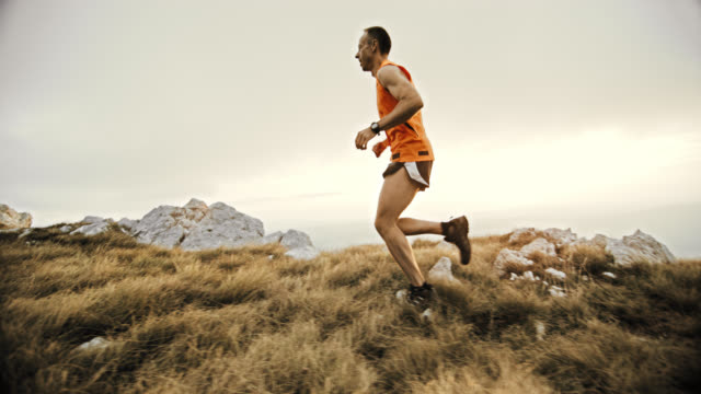 slo mo trail running on the mountain - side view stock videos & royalty-free footage