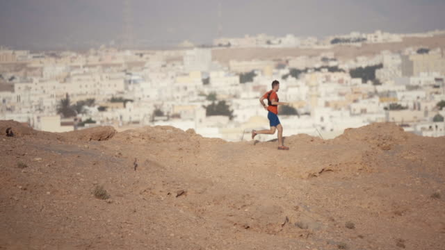 Trail running striding across mountain ridge above Middle Eastern town