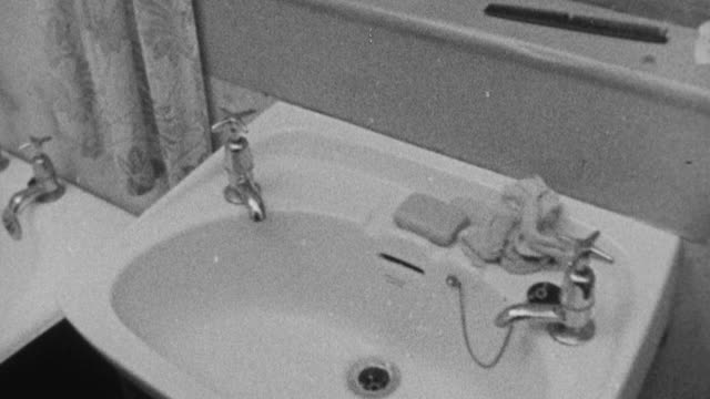 1972 montage trailer bathroom containing tub, sink, and toilet, with gypsy sitting at kitchen table talking / bushey, england, united kingdom - domestic bathroom stock-videos und b-roll-filmmaterial
