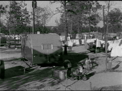 Trailer camp w/ laundry drying on clotheslines between trees children outside MS 'Du Pont Operations' sign LA WS Savannah River plant amp full...