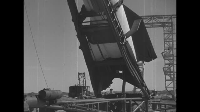 trailer lift raises v-2 rocket to vertical position at its launch pad; pan up and down the length of the v-2, which will be fired with a camera... - note pad点の映像素材/bロール