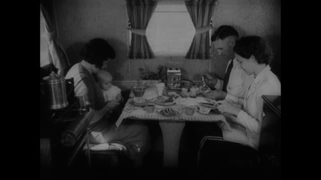vidéos et rushes de trailer table kitchen couch woman cooking at stove male hands lighting heater w/ match icebox & ice middle class family eating at table convertible... - stéréotype de la classe moyenne