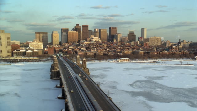 vídeos de stock e filmes b-roll de ws ha train and traffic on longfellow bridge crossing frozen charles river, city skyline in background / boston, massachusetts, usa - 1993