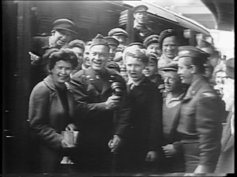 train approaches station / crowd surrounds bob hope in military uniform / hope jokes with crowd and speaks into mic / hope tips his hat and walks... - ボブ ホープ点の映像素材/bロール