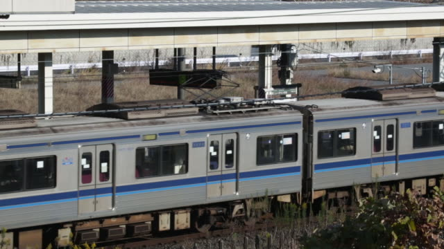 a train arrives as morning commuters wait on the platform of a train station in inzai chiba prefecture japan on tuesday dec 9 morning commuters wait... - veicolo terrestre commerciale video stock e b–roll