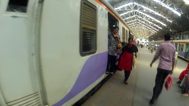 A train arrives at Churchgate Station in Mumbai, and commuters disembark.