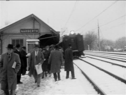 B/W 1955 train arriving at snowy train platform marked 'NARBERTH' / people walking on platform