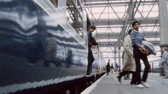 1978 montage train arriving at station during rush hour as commuters disembark and flood the station / united kingdom - station stock videos & royalty-free footage