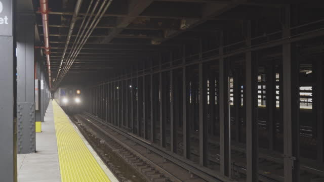 a train arriving at the 64th street trainstation train station deserted because of covid-19 coronavirus outbreak. new york city, usa. - subway train stock videos & royalty-free footage