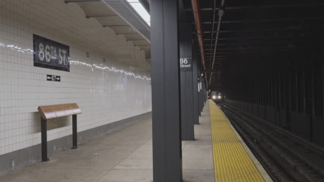 a train arriving at the 64th street trainstation train station deserted because of covid-19 coronavirus outbreak. new york city, usa. - tunnel stock videos & royalty-free footage