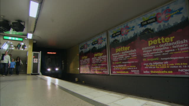 ws pan train arriving at underground station with people passing by / stockholm, stockholm, sweden - 階段点の映像素材/bロール