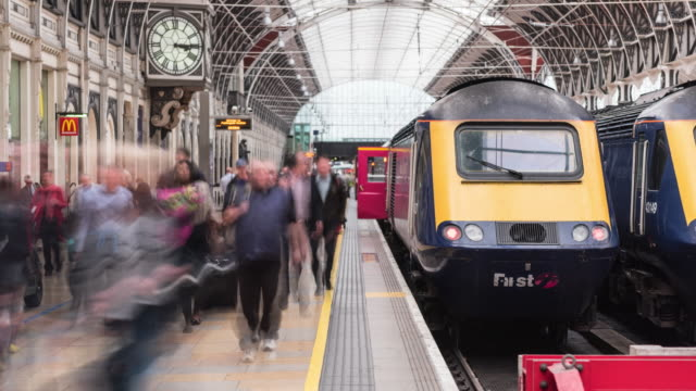 vídeos de stock e filmes b-roll de train arriving with commuters time lapse - reino unido