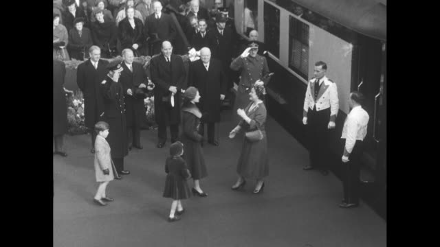 train bearing queen mother elizabeth arrives at waterloo station in london as royal family waits on platform and vips sit in bleacher-type seats... - エリザベス・ボーズ=ライアン点の映像素材/bロール
