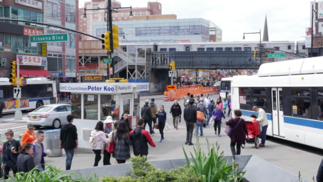 train, bus traffic and people walking in flushing, queens, new york city - queens stock-videos und b-roll-filmmaterial