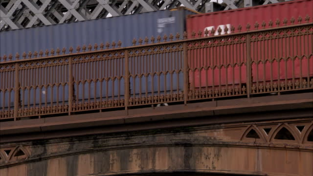A train carries shipping containers across a viaduct. Available in HD.