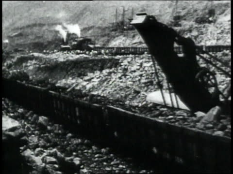 ws train cars going by rocky terrain carrying debris followed by the steam engine / republic of panama - anno 1906 video stock e b–roll