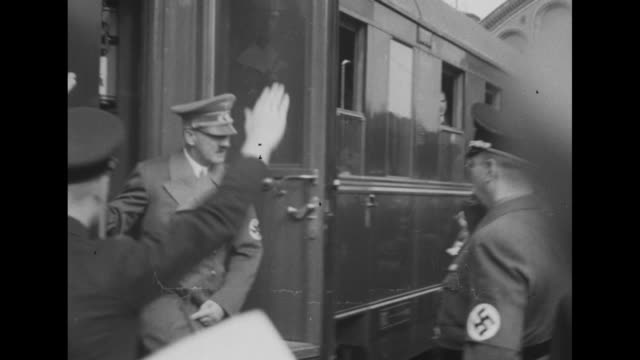 Train coming down tracks past camera / Nazi officials waiting on platform as train pulls up / Adolf Hitler getting off train and being greeted by...