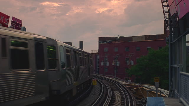 vídeos de stock, filmes e b-roll de ms el train coming toward camera on curved track at dusk / chicago, illinois - metrô de chicago