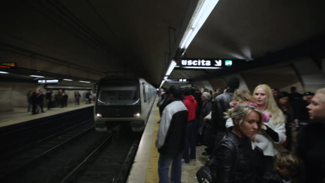 ms pan train coming towards platform in subway / rome, italy - metropolitana video stock e b–roll