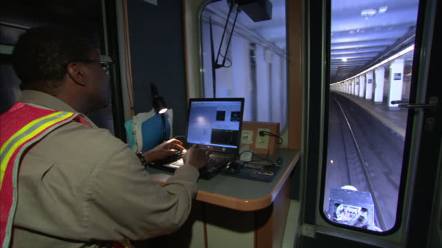 a train conductor uses a laptop as he controls the subway train. - transport conductor stock videos & royalty-free footage