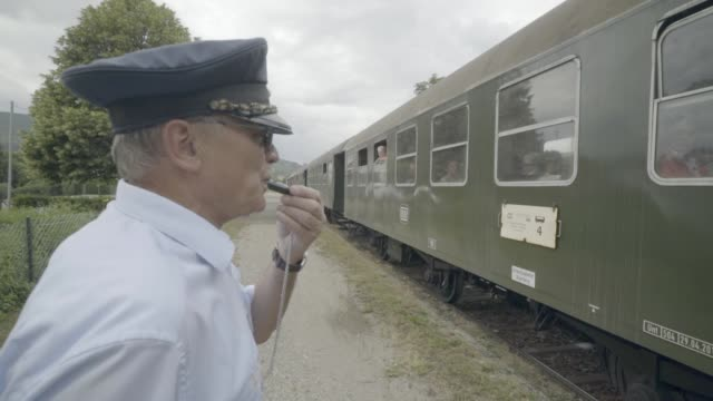 train conductor walks along an old steam train and blows his whistle - fischietto video stock e b–roll