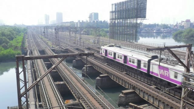 vidéos et rushes de a train crosses a bridge along a railway track in mumbai india on sunday jan 28 passengers stand in the doorways of a train carriage in mumbai - voie ferrée