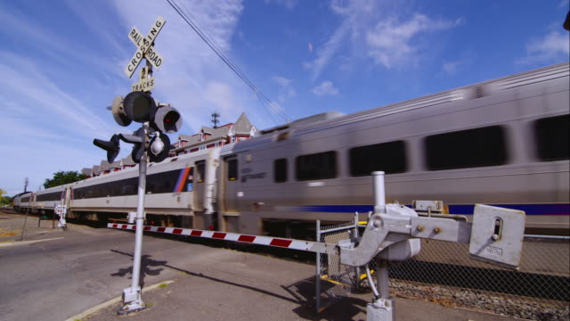 stockvideo's en b-roll-footage met train crosses an active railroad crossing - new jersey