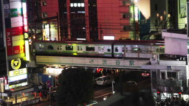 train crosses over busy street in tokyo. - cross stock videos & royalty-free footage
