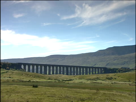 train crosses ribblehead viaduct under blue sky in english countryside; pennine way england - yorkshire england stock videos & royalty-free footage