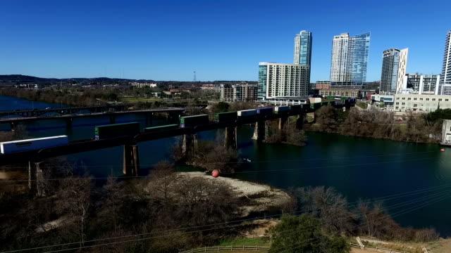 Tren cruza el río Colorado en Ciudad Lago de Austin, Texas, en el centro de la ciudad de condominios en el norte y del Texas Colina País en el fondo