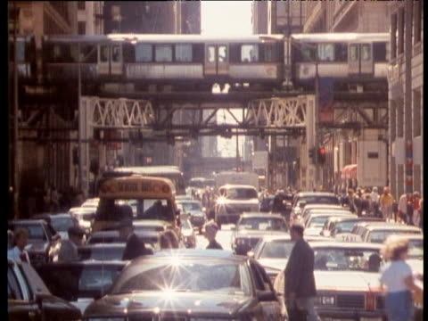 L (elevated) train crossing above a busy Chicago street jammed with traffic and people