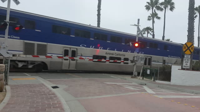 train crossing gate on the coast train speeds by camera - level crossing stock videos & royalty-free footage