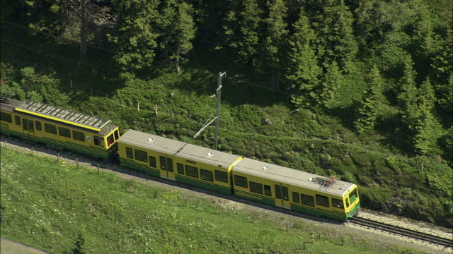 AERIAL TS ZO Train crossing green hills near Wengen, Bern, Switzerland