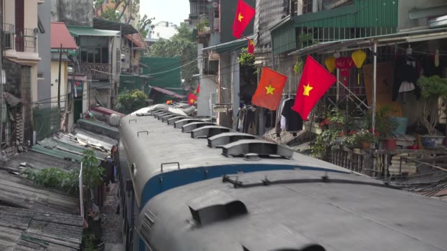 train crossing hanoi narrow street high angle view. iconic image of narrow street with the railway in the middle of the buildings. hoàn kiếm district - narrow stock videos & royalty-free footage