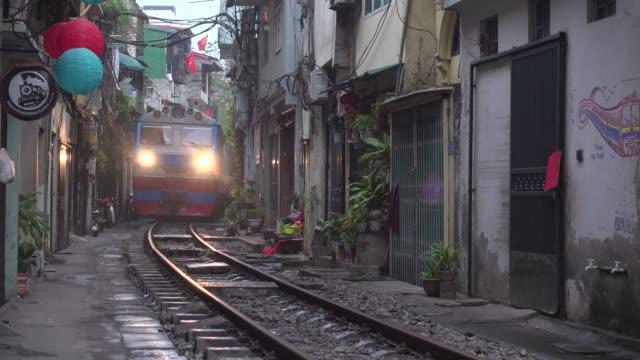 train crossing narrow street at hanoi with vietnam flags. trần phú street point of view. hoàn kiếm district - north vietnam stock videos & royalty-free footage