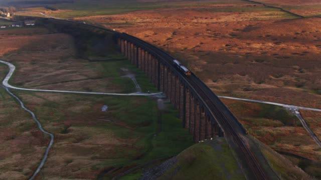 train crossing ribblehead viaduct at sunset - drone shot - british culture stock videos & royalty-free footage