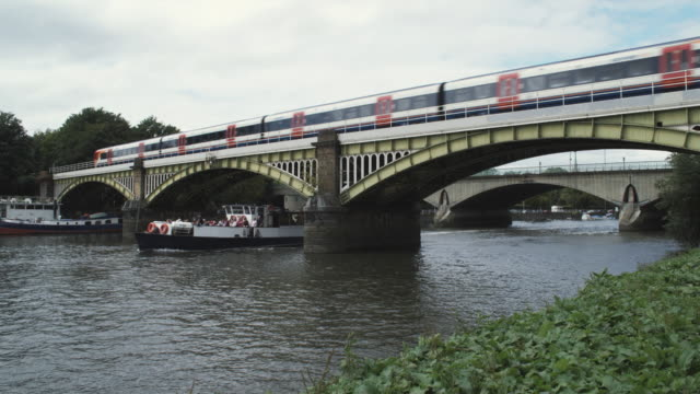 ws train crossing richmond bridge, river sightseeing boat passing underneath / richmond, london, united kingdom - rosso stock videos & royalty-free footage