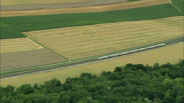 vidéos et rushes de aerial train crossing rural landscape, neuchatel, vaud, switzerland - patchwork landscape