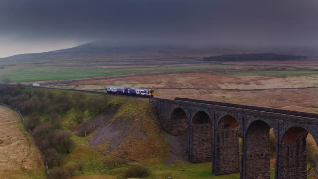 train crossing viaduct and arriving in ribblehead station - drone shot - yorkshire england stock videos & royalty-free footage